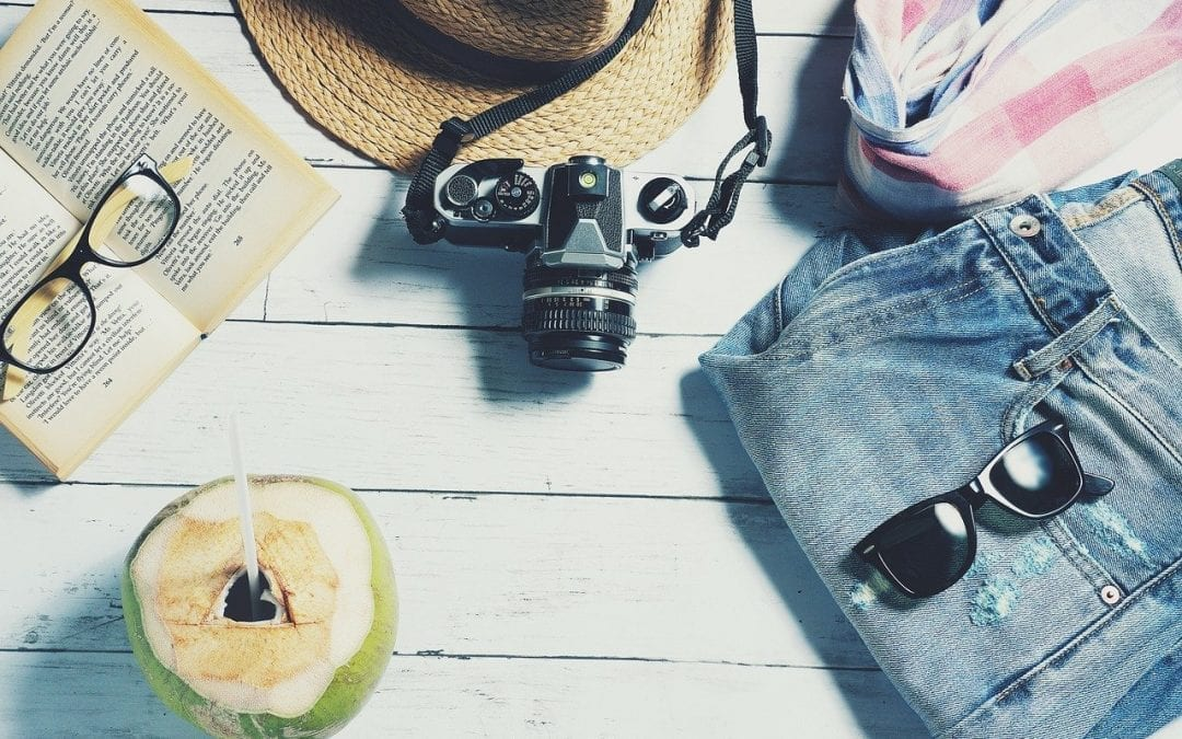 a book, camera, sunglasses, and coconut drink arranged on a table